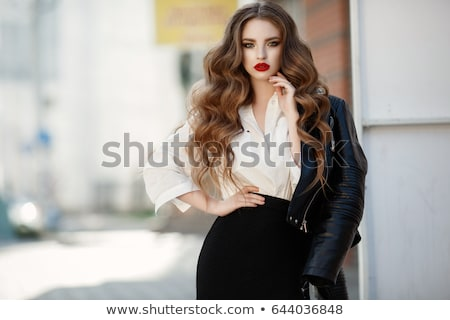 Stock photo: Fashionable beautiful woman posing on red background.