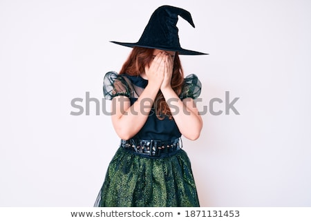 sad young woman in witch halloween costume wearing hat stock photo © deandrobot
