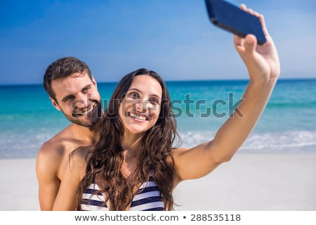 woman in swimsuit taking selfie with smatphone Stock photo © dolgachov