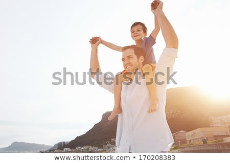 Father carrying son piggyback outdoors Stock photo © IS2