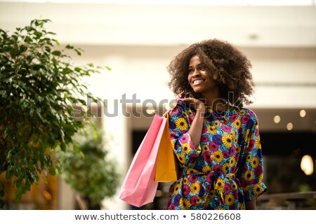 Cheerful young lady in black dress holding shopping bags. Stock photo © deandrobot