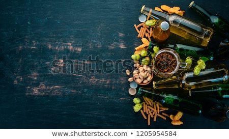 Glass of lager beer with pistachios nuts on stone board on black background. Beer and snack.  stock photo © DenisMArt