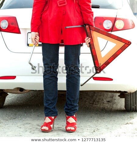 Woman holds red triangle sign and wrench and waits for roadside  Stock photo © Nobilior