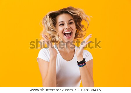 Photo of surprised woman in basic clothing screaming and laughin Stock photo © deandrobot