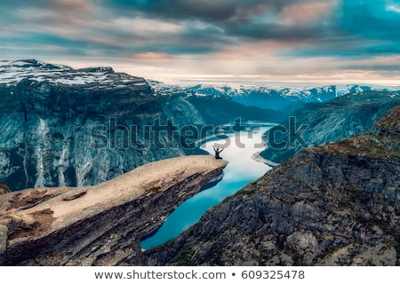 man with his arms in the air on the top of a rock Stock photo © nito
