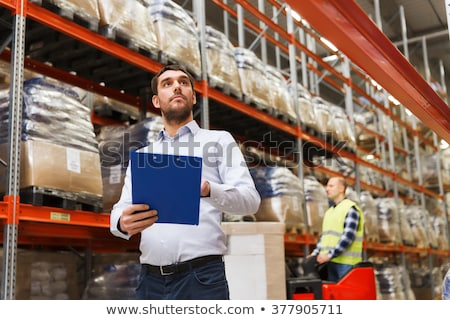 worker and businessman with clipboard at warehouse Stock photo © dolgachov