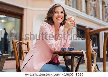 attractive woman in romantic mood smiling in happiness sitting at table wearing pink jacket, stylish Stock photo © ElenaBatkova
