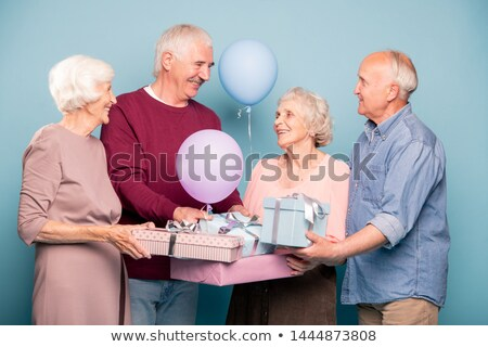 Cheerful company of friendly pensioners with balloons and giftboxes Stock photo © pressmaster