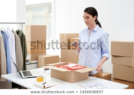 Young female shop-assistant photographing parcel with folded casualwear Stock photo © pressmaster
