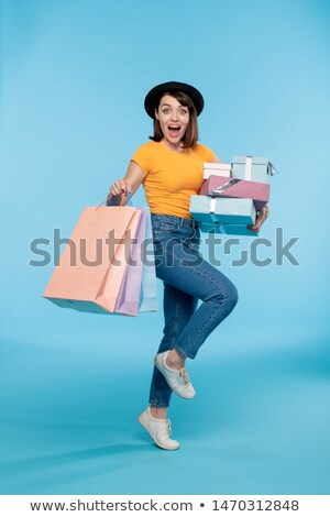 Young excited shopaholic with giftboxes and paperbags Stock photo © pressmaster