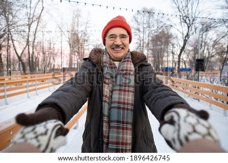 Active mature man with camera photographing his happy wife with trekking sticks Stock photo © pressmaster