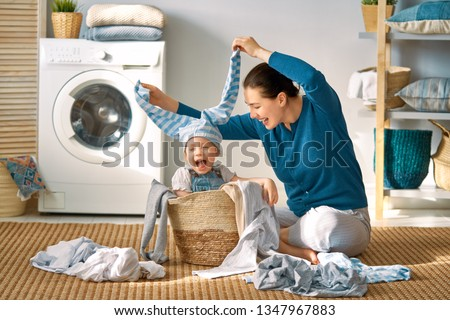 Happy child helper and mother have fun in laundry room, do washi Stock photo © vkstudio