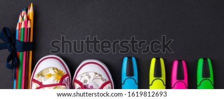 Banner of Set of colored pencils wrapped in a blue ribbon near sneakers and marker on black wooden b Stock photo © Illia