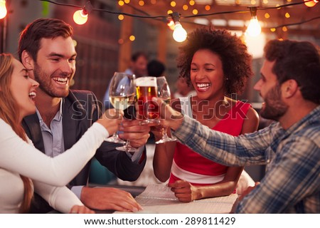 Front view of group of multi ethnic friends toasting beer bottles while sitting on the beach in the  Stock photo © wavebreak_media