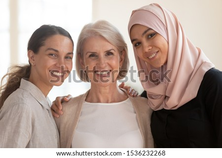 Portrait of pretty multinational women looking at camera and hugging Stock photo © deandrobot