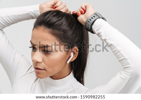Image of young brunette sportswoman in earpods tying her hair Stock photo © deandrobot