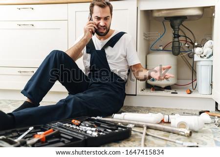 Negatieve man loodgieter werk uniform binnenshuis Stockfoto © deandrobot