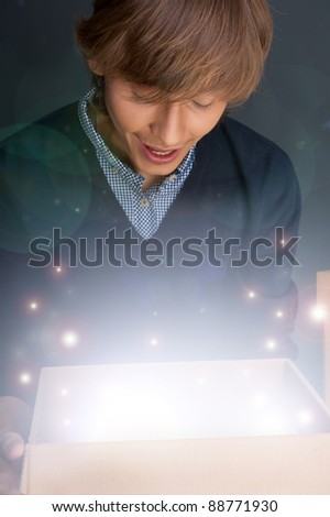 Portrait of young man opening gift box. He is happy. Magical shi Stock photo © HASLOO