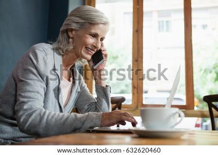 happy senior woman talking on smart phone while sitting at beach stock photo © wavebreak_media