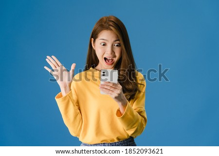 Surprised pretty lady in casual clothes using smartphone isolated Stock photo © deandrobot
