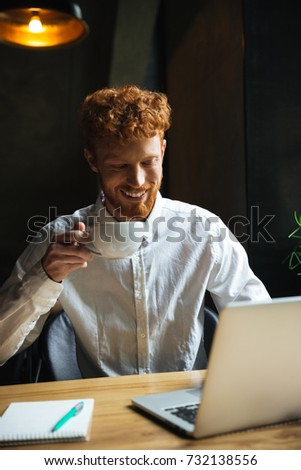 Young smiling handsome readhead bearded man in white shirt using Stock photo © deandrobot