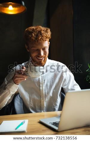 utilisant · un · ordinateur · portable · souriant · séance · fauteuil · salon - photo stock © deandrobot