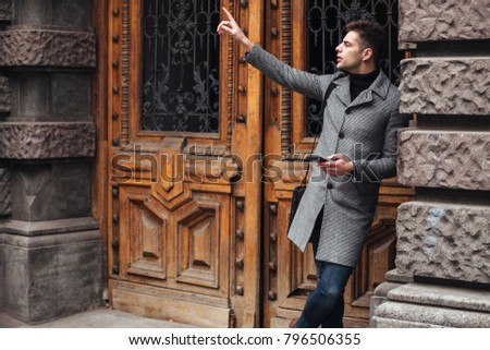 Serious good-looking man standing near old building using cell p Stock photo © deandrobot