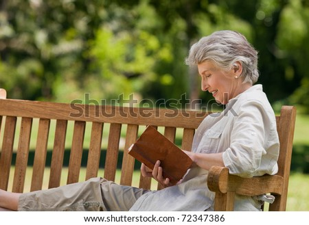 Portrait of a senior woman sitting in the grass reading a book Stock photo © FreeProd