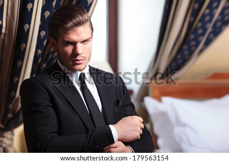 handsome businessman sitting on chair fixes his tuxedo sleeve Stock photo © feedough