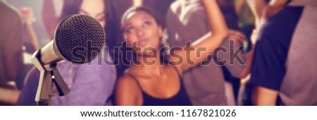 Microphone with stand against female friends dancing in nightclub Stock photo © wavebreak_media