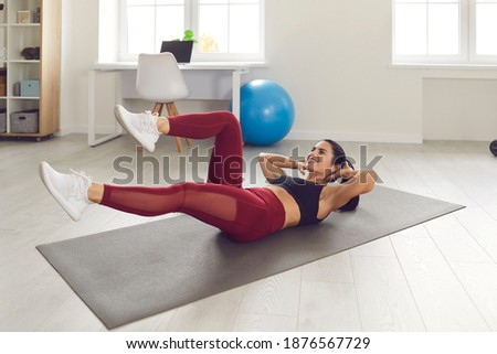 Cheerful sportswoman lying on the floor and doing fitness exercise Stock photo © deandrobot