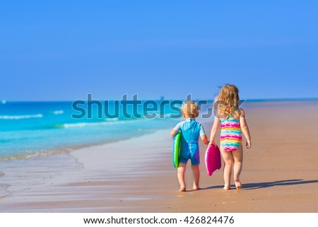 little girls with surfing boards playing on tropical ocean beach stock photo © dashapetrenko