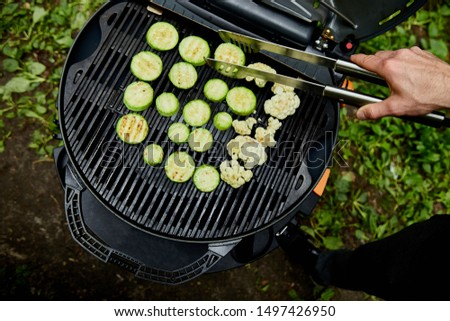 Hand of young man grilling zucchini vegetable on huge gas grill .  Stock photo © Illia