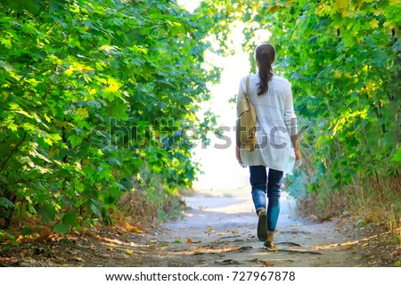 A young woman is walking along a forest road Stock photo © galitskaya