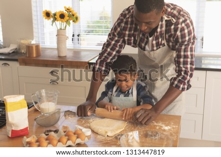 Front view of African American father and son rolling out cookie dough in kitchen at home Stock photo © wavebreak_media