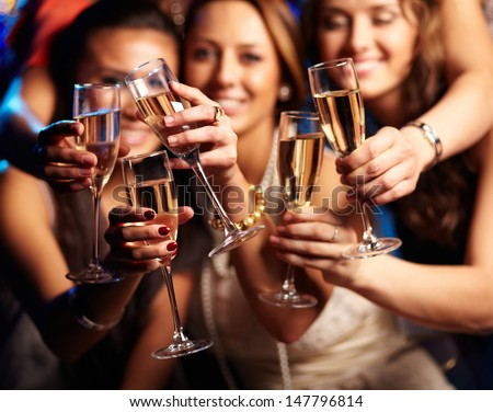 Group of friends holding flutes of sparkling champagne and burning bengal lights Stock photo © pressmaster