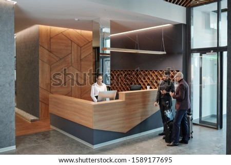 Two elegant businessmen with baggage using smartphones in hotel lounge Stock photo © pressmaster