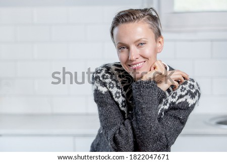 Beautiful brunette European woman with makeup, tender smile, dressed in knitwear, enjoys comfort, po Stock photo © vkstudio