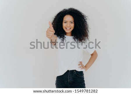 Photo of happy curly woman with crisp hair raises thumb up, gives approval, says sounds good, makes  Stock photo © vkstudio