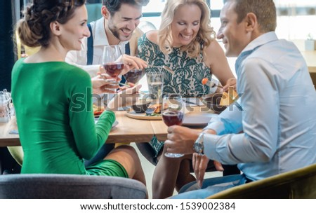 Friends in a restaurant having a jolly good time enjoying the food Stock photo © Kzenon