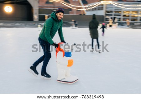 Delightful male skates on skate ring with help of special aid, p Stock photo © vkstudio