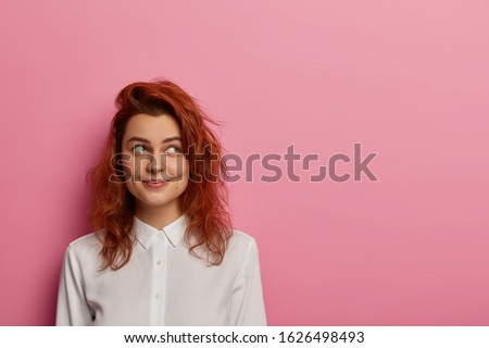 Indoor shot of pleased beautiful ginger woman has positive facial expression, dressed in black cloth Stock photo © vkstudio