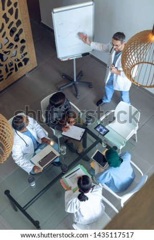 High angle view of matured Caucasian male physician and senior Caucasian couple discussing over lapt Stock photo © wavebreak_media