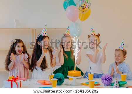 Overjoyed children friends clap hands and looks at big sparkle on cake, stand near festive table wit Stock photo © vkstudio