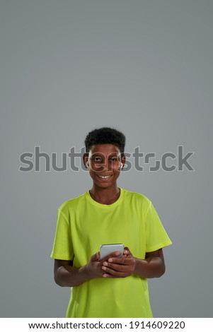 Image of joyful sportsman holding smartphone while sitting on yo Stock photo © deandrobot