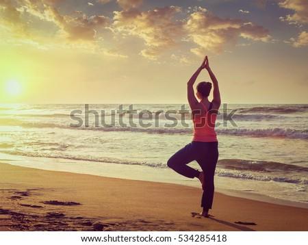 Young sporty fit woman doing yoga tree asana on beach Stock photo © dmitry_rukhlenko