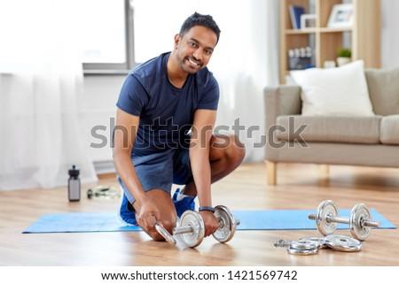 smiling indian man assembling dumbbells at home Stock photo © dolgachov