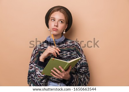 Photo of pretty thinking woman making notes in diary Stock photo © deandrobot