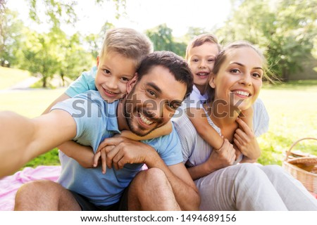 family having picnic and taking selfie at park Stock photo © dolgachov