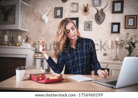 Busy businesswoman with laptop, coffee and food talking on phone in her office stock photo © wavebreak_media
